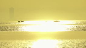 Sunset and Fishing boats. You can see a phantom tower behind stock footage