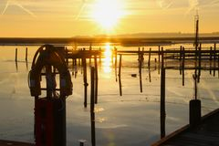 Sunset at the fishing stakes in the harbor Royalty Free Stock Photo