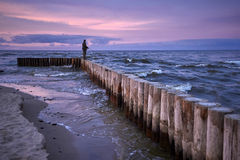 Sunset fisshing on breakwater Royalty Free Stock Images