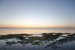Sunset at a flat rock coast Stock Image