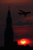 Sunset flight. Airplane flying over the city during sunset hour Royalty Free Stock Image