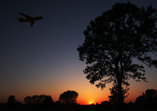 Sunset flight. An airplane taking off at sunset Stock Photo