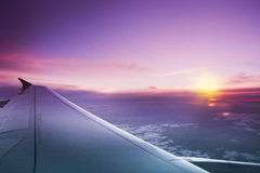Sunset flight. Above sky airplane wing, airplane trip royalty free stock photography