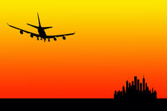 Sunset flight. An airplane preparing to land near the city during sunset hour Stock Images