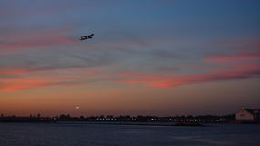 Sunset Flight Departing LaGuardia Airport NYC. Plane taking off from La Guardia Airport at sunset during the summer Stock Photo