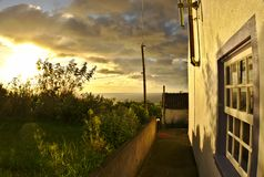 Sunset on Flores Island with a pretty house in the foreground Azores Portugal royalty free stock photography