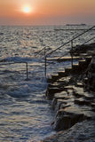 Sunset and flow on the rocky beach. Sunset at flow sea in Croatia Royalty Free Stock Photo