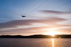 Sunset flying #2. Airplane in the sunset over the water with blue sky and hills in the background Stock Photography