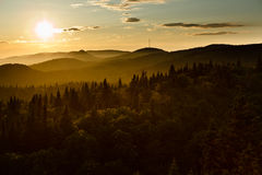 Sunset in the fog. The sun is going down on the foggy mountains in the Parc Forillon, Quebec, Canada Stock Photo