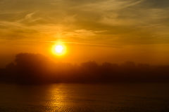 Sunset in a foggy summer evening. Horizontal view of a sun-setti Royalty Free Stock Image