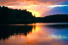 Sunset on the forest lake. Sunset painted the sky and water of the river in bright colors dramatic Stock Image