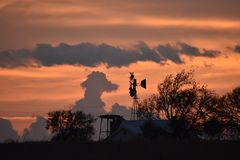 Sunset in Fort Worth. This image was taken at sunset in FT Worth Texas. Is it me or does that cloud look like a dog looking at the windmill royalty free stock photos