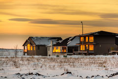 Sunset in the fridged prairies. The glowing warm color of the sunset reflecting on the windows of the houses in the vast snow covered flat lands of Saskatchewan stock photos