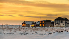 Sunset in the fridged prairies. The glowing warm color of the sunset reflecting on the windows of the houses in the vast snow covered flat lands of Saskatchewan stock photography