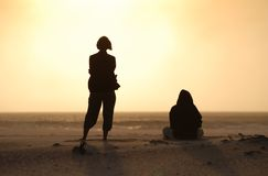 Sunset friends. Friends watch sunset at windswept Noordhoek Beach, Cape Town Stock Images
