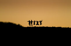 Sunset friends. Silhouette of friends jumping in sunset at beach Stock Images