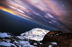 Sunset frosty night landscape deep blue Arctic Ocean. Northern cold winter nature cliffs and clouds, black rocky coast. Sunset frosty night landscape deep blue royalty free stock image