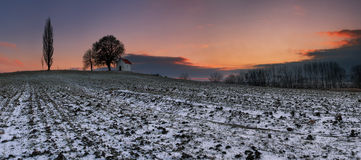 Sunset on frozen field with a chapel. Royalty Free Stock Photo