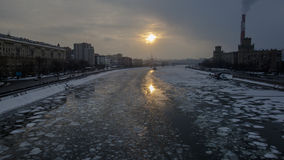 Sunset on the frozen river in city Stock Photos