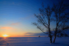 Sunset on frozen sea shore Stock Images