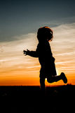 Sunset Child Silhouette. A silhouette of a child having fun with soap bubbles in the sunset Royalty Free Stock Image