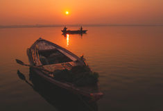 Sunset at Ganges. Two men in a rowing boat, and one abandoned boat on the ganges in Varanasi, India royalty free stock image