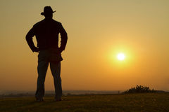 Cowboy gazing into the sunset. Male looking out to the sunset horizon Stock Photo