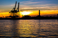 Sunset at Genoa`s port, silhouette of the Lanterna, Italy Stock Images