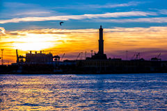 Sunset at Genoa`s port, silhouette of the Lanterna, Italy Royalty Free Stock Photo