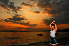 Sunset girl. Beautiful girl posing by the sea at sunset Royalty Free Stock Photography
