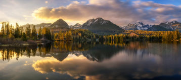 Sunset about glacial lake named Strbske Pleso in National Park H. Sunset panorama of glacial mountain lake named Strbske Pleso in National Park High Tatras royalty free stock images