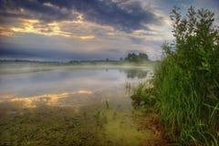 Sunset of gloomy lake Stock Image