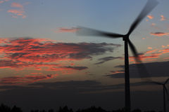 In the sunset glow in the background of a wind turbine in the power generation. In the background of the red glow of the sunset, wind turbines in power Royalty Free Stock Photo
