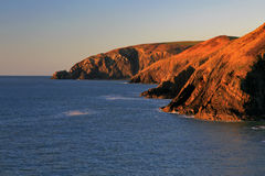 Sunset glow highlighting the rock strata in cliffs. Sunset glow highlighting the rock strata in the cliffs of the Pembrokeshire coastline from Ceibwr Bay Stock Photos