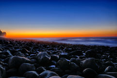 Sunset Glow Over Beach Rocks. Stock Images