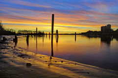 Sunset glow over the river and beach, with smooth water surface Royalty Free Stock Photography