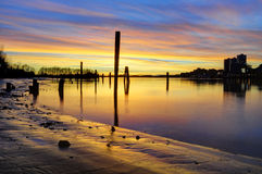 Sunset glow over the river and beach, with smooth water surface Stock Photo