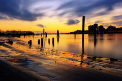 Sunset glow over the river and beach, with smooth water surface Royalty Free Stock Photos