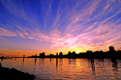 Sunset glow with silhouette of a city by a river Stock Photo