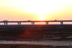 The sunset glow, the world's longest bridge have vehicles in traffic. Sunset, the bridge on the tidal flat, there are vehicles on the road Royalty Free Stock Images