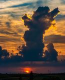 Sunset with glowing sky and a tower of clouds royalty free stock image