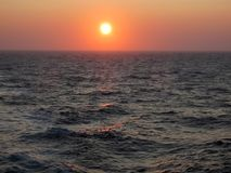 Sunset Glows Orange over Rough Ocean Surface. Sunset glows orange on the horizon.  The ocean surface is rough and picks up some of the orange glow Royalty Free Stock Photos