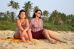 Sunset in Goa. Two pretty girls sitting on the beach sand over sunset in Goa stock photography