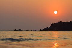 Sunset in Goa. With a silhoutte of a fisher on rocks Royalty Free Stock Photo
