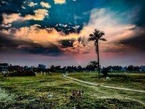 Sunset and golden cloudy sky. Over the play ground in rural India royalty free stock photography