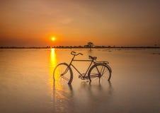 Sunset golden hours moment alone bike. This sunset golden hours moment , yellow sky and gold sunset magic bike stock photos