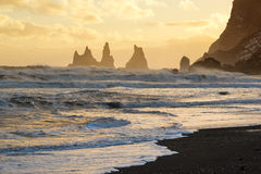 Sunset with golden sky behind the Reynisdrangar rocks, Vik black sand beach, Iceland Stock Photography
