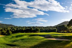 Sunset golf course with trees, blue sky and clouds stock image