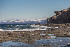 Sunset Gros Morne National Park. Snow capped hills in the distance at sunset against a clear blue sky. White rapids and rocks in the sea. Large craggy cliffside Royalty Free Stock Image