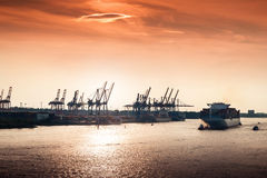 Sunset at Hamburg harbor. Container Terminal and leaving cargo ship at sunset in the port of Hamburg Stock Photo
